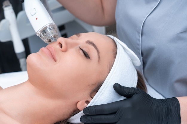 Jonge vrouw die laserbehandeling in cosmetologiekliniek ontvangt