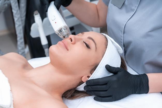 Jonge vrouw die laserbehandeling in de kosmetiekkliniek ontvangt