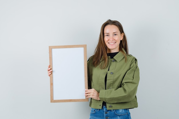 Jonge vrouw die leeg frame in groen jasje houdt en blij, vooraanzicht kijkt.