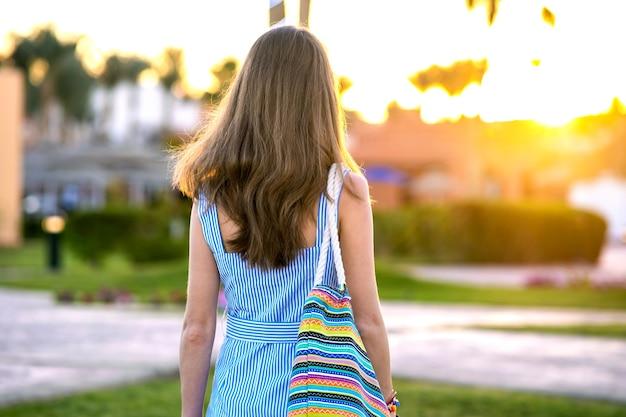 Jonge vrouw die lichtblauwe de zomerkleding draagt die modieuze schoudertas houdt