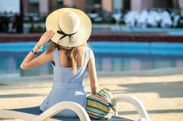 Jonge vrouw die lichte de zomerkleding en de gele zitting van de strohoed buiten dragen dichtbij hotel zwembad op de zomer zonnige dag.