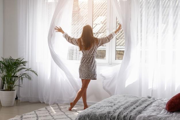 Jonge vrouw die lichte gordijnen in slaapkamer thuis opent