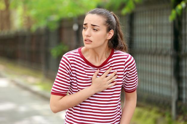 Jonge vrouw die lijdt aan een hartaanval buitenshuis