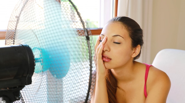 Jonge vrouw die lijdt aan een hittegolf met behulp van een ventilator zittend op een bank in de woonkamer thuis.
