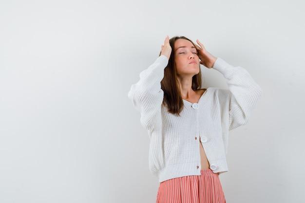 Jonge vrouw die lijdt aan hoofdpijn in vest en rok op zoek vermoeid geïsoleerd