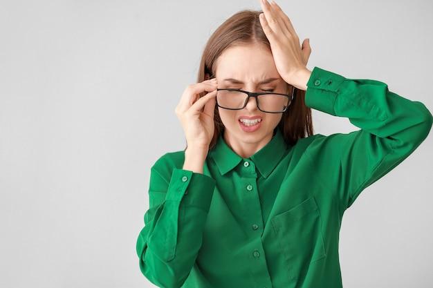Jonge vrouw die lijdt aan hoofdpijn op grijs