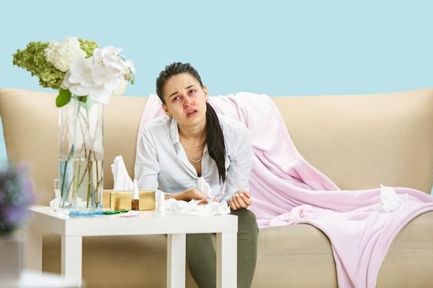 Jonge vrouw die lijdt aan huisstofmijt of seizoensgebonden allergie. niezen in het servet en zittend omringd door gebruikte servetten op de vloer en bank. medicijnen slikken zonder resultaat. gezondheidszorgconcept.