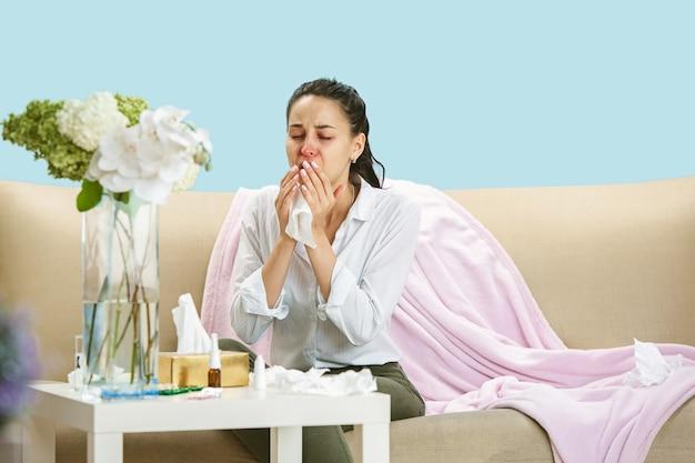 Jonge vrouw die lijdt aan huisstofmijt of seizoensgebonden allergie niezen in het servet