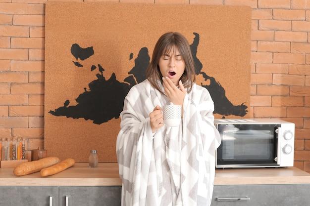 Jonge vrouw die lijdt aan slaapgebrek in de keuken