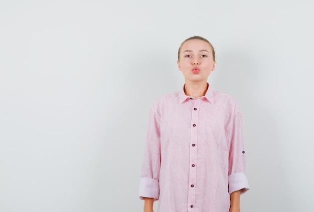 Jonge vrouw die lippen houdt die in roze overhemd worden gevouwen en mooi kijken
