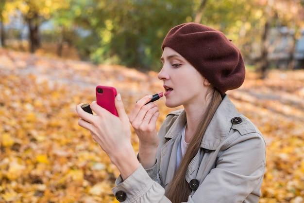 Jonge vrouw die lippenstift op haar lippen toepast