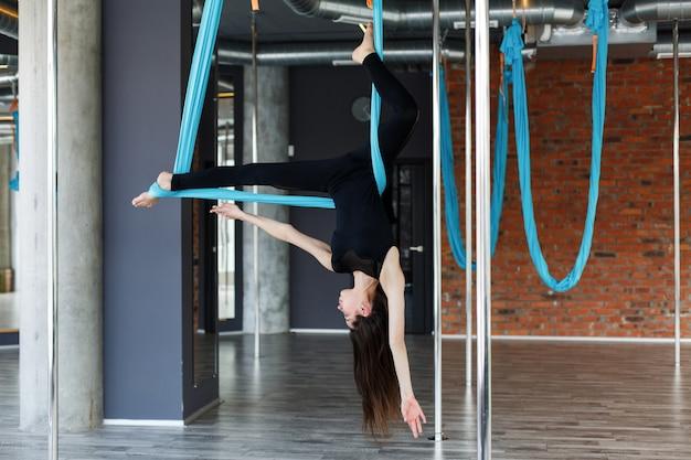 Jonge vrouw die luchtyoga op blauwe hangende hangmat in de gymnastiek doen