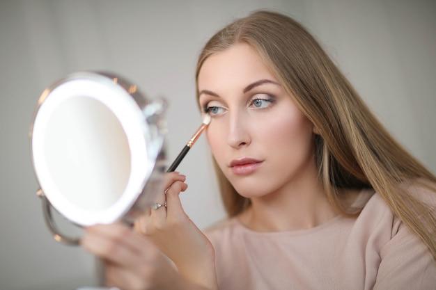 Jonge vrouw die make-up aanbrengt