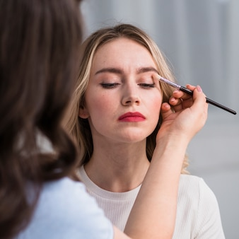Jonge vrouw die make-up toepast door gezichtskunstenaar