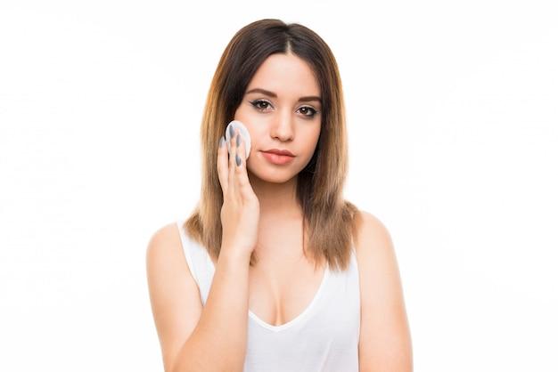 Jonge vrouw die make-up verwijdert uit haar gezicht met katoenen stootkussen