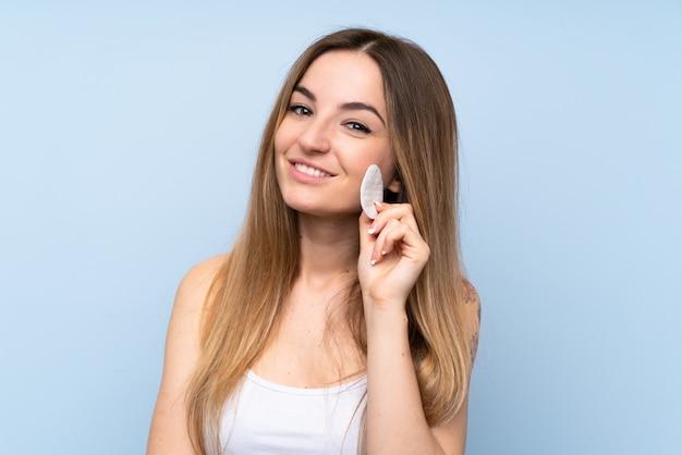 Jonge vrouw die make-up verwijdert uit haar gezicht met wattenschijfje