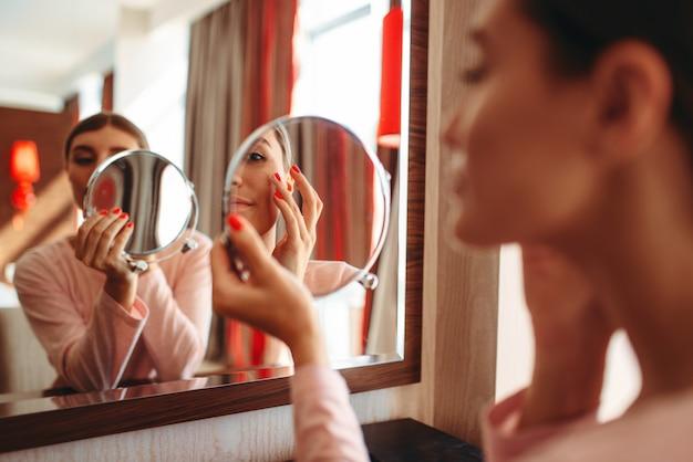 Jonge vrouw die make-up voor de spiegel in de slaapkamer doet.