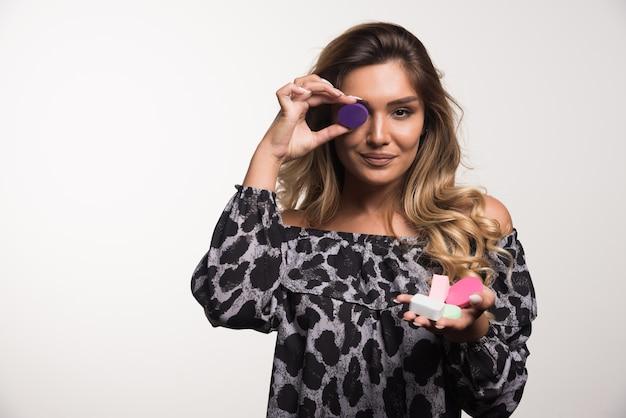 Jonge vrouw die make-upsponzen gelukkig op witte muur toont.