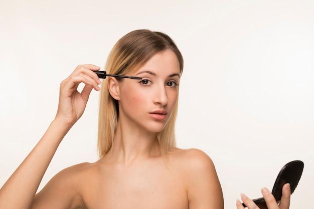 Jonge vrouw die mascara gebruikt