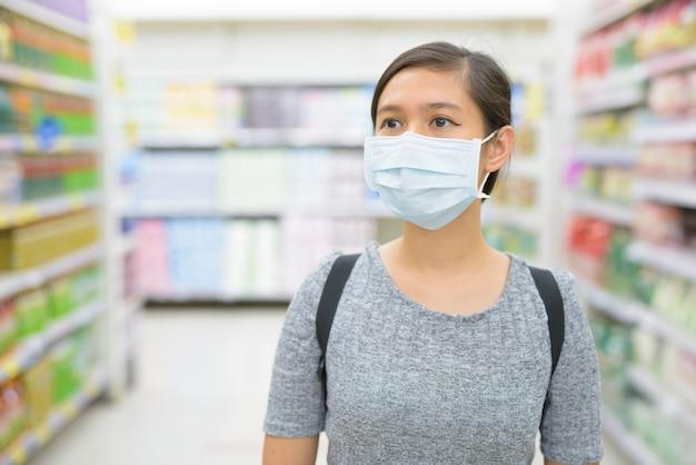 Jonge vrouw die masker draagt en met afstand bij de supermarkt winkelt