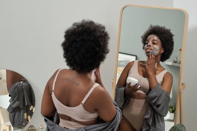 Jonge vrouw die masker op gezicht voor spiegel toepast