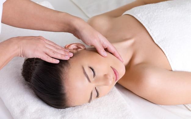 Jonge vrouw die massage voor de huid van haar mooi gezicht heeft