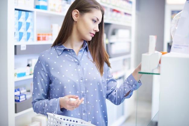 Jonge vrouw die medicijnen koopt bij gezondheidswinkel