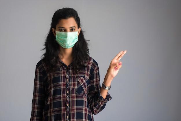 Jonge vrouw die medisch gezichtsmasker draagt dat teken toont. vrouw die chirurgisch masker voor coronavirus draagt.