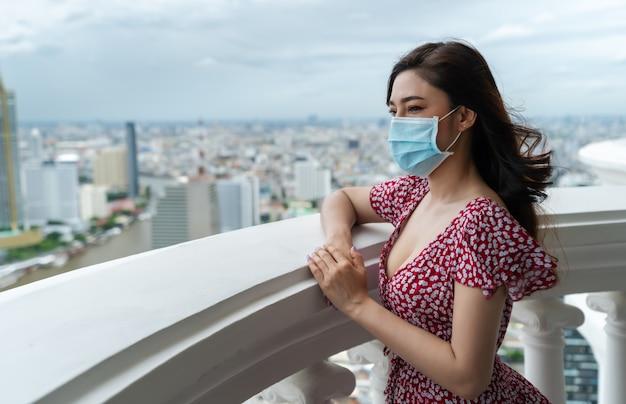 Jonge vrouw die medisch masker draagt ter voorkoming van coronavirus (covid-19) en uitzicht op de stad kijkt