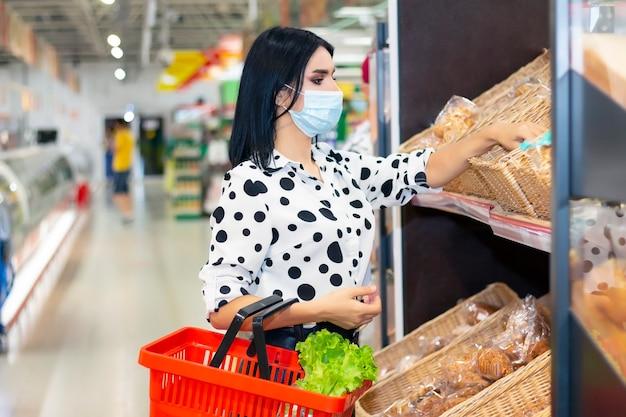Jonge vrouw die medisch wegwerpmasker draagt dat in de supermarkt winkelt tijdens de uitbraak van coronaviruspneumonie. bescherming en voorkom maatregelen tijdens epidemische tijd.