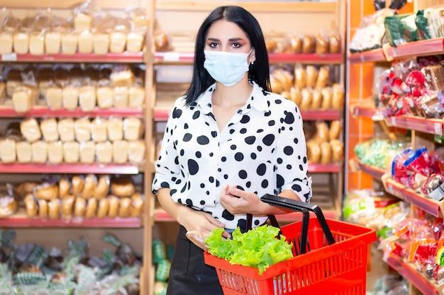 Jonge vrouw die medisch wegwerpmasker draagt dat in de supermarkt winkelt tijdens de uitbraak van coronaviruspneumonie. bescherming en voorkomen van maatregelen tijdens epidemische tijd.