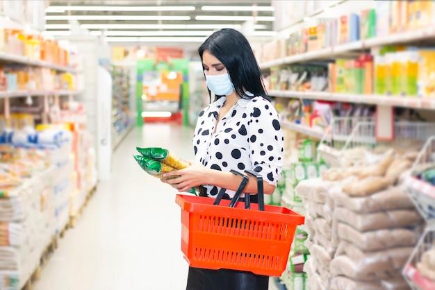 Jonge vrouw die medisch wegwerpmasker draagt dat in de supermarkt winkelt tijdens de uitbraak van coronaviruspneumonie