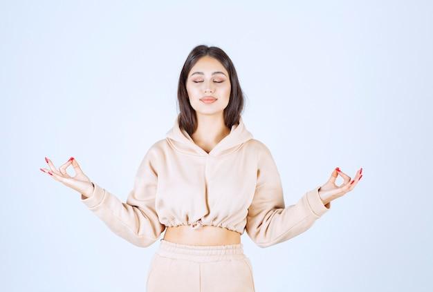 Jonge vrouw die meditatie doet en handhoudingen toont