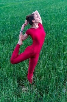 Jonge vrouw die mediteert in het grasveld