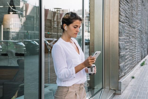 Jonge vrouw die meeneemkoffiekop houdt die mobiele telefoon met behulp van