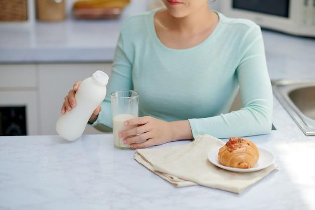 Jonge vrouw die melk in glas giet met ontbijt