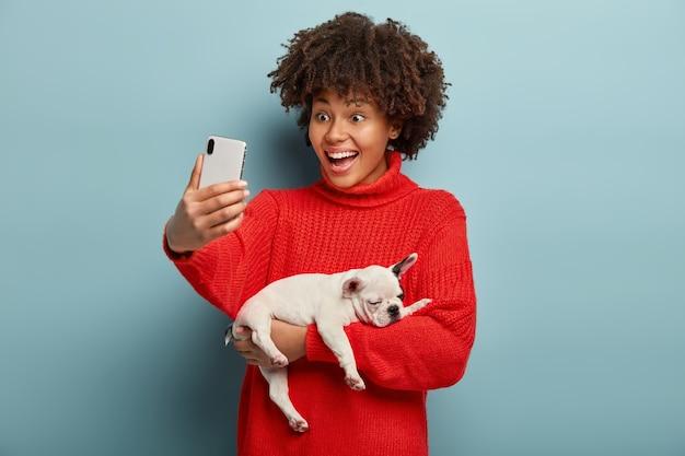 Jonge vrouw die met afro-kapsel hondje houdt