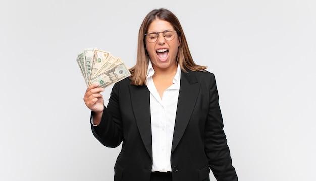 Jonge vrouw die met bankbiljetten agressief schreeuwt, zeer boos kijkt