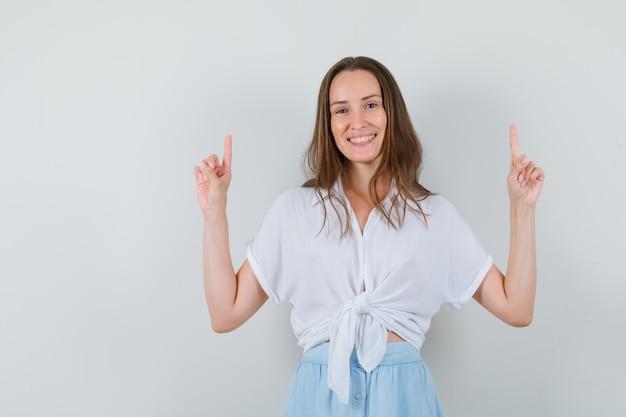 Jonge vrouw die met beide wijsvingers in witte blouse en lichtblauwe rok benadrukt en vrolijk kijkt