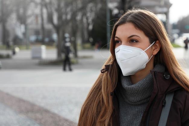 Jonge vrouw die met beschermend gezichtsmasker ffp2 kn95 in stadsstraat loopt