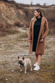 Jonge vrouw die met buldoghuisdier loopt in park