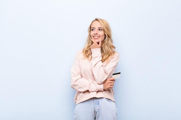Jonge vrouw die met creditcard met een gelukkige zekere uitdrukking glimlacht