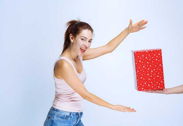 Jonge vrouw die met de hand vooruit verlangt om de rode geschenkdoos te pakken