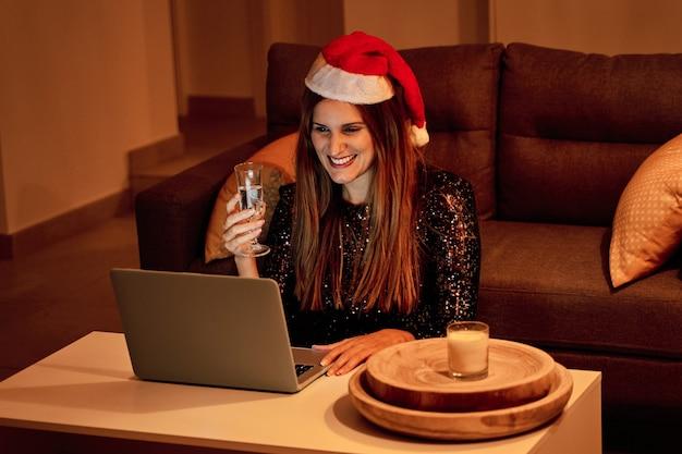 Jonge vrouw die met de hoed van de kerstman een videogesprek voert met haar familie om kerstmis te vieren. concept van eenzaamheid, gescheiden gezin, sociale afstand en kerstmis.