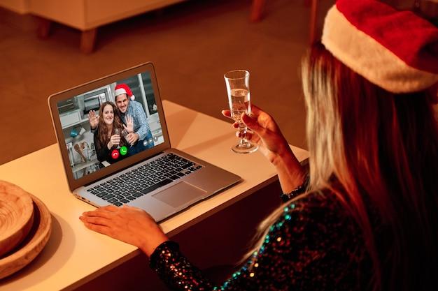 Jonge vrouw die met de hoed van de kerstman een videogesprek voert met haar familie om kerstmis te vieren.