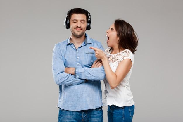 Jonge vrouw die met de mens in hoofdtelefoons over grijze muur boos maken