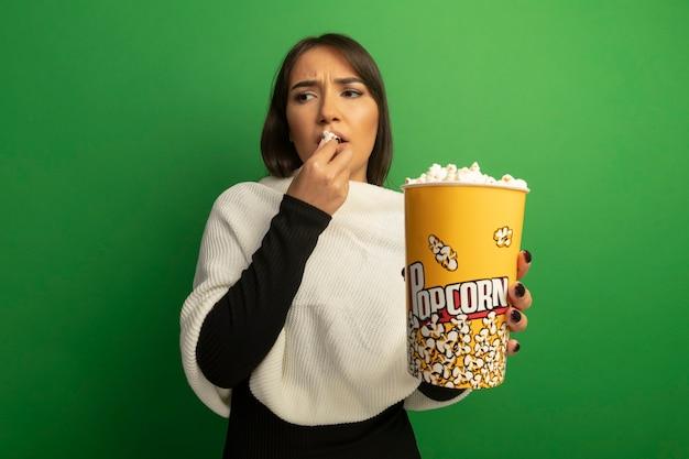 Jonge vrouw die met de witte emmer van de sjaalholding met popcorn het eet die het verward kijkt