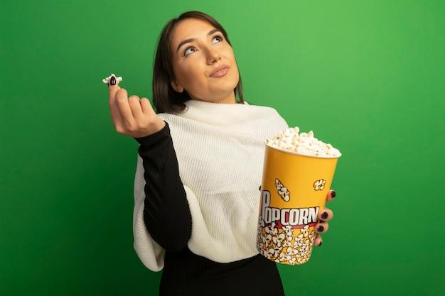 Jonge vrouw die met de witte emmer van de sjaalholding met popcorn in verwarring omhoog kijkt