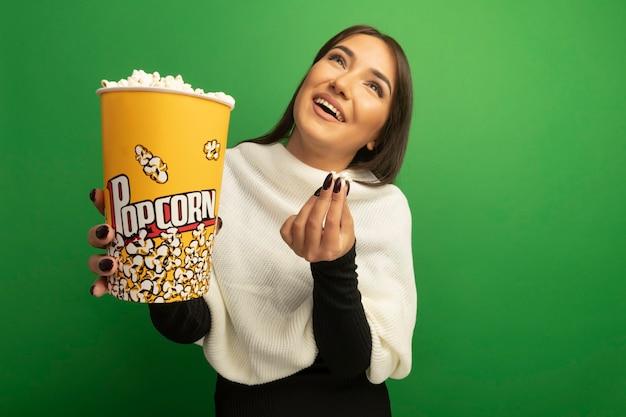 Jonge vrouw die met de witte emmer van de sjaalholding met popcorn omhoog het glimlachen happyand positief kijkt