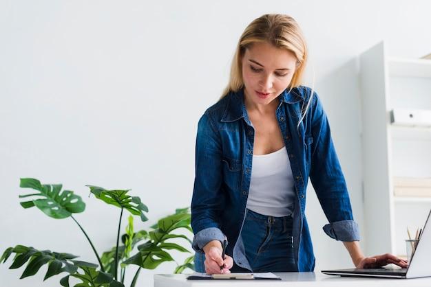 Jonge vrouw die met documenten in bureau werkt